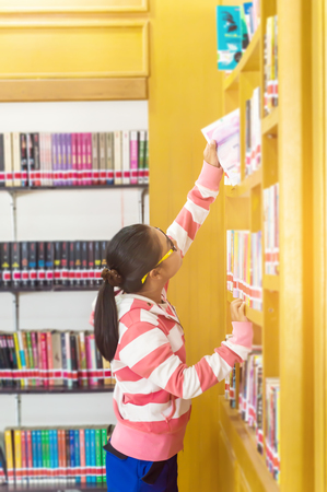 Asian young college student teenager smile with school folders reading book at library high school university campus college knowledge center for study learning and bright idea in summer holiday.Education concept. Stock Photo