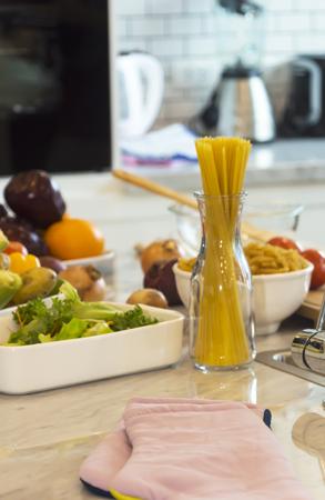 Gros spaghetti et légumes avec des ingrédients prêts à être cuits dans la salle de cuisine moderne meubles blancs. Banque d'images