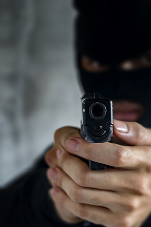 Masked robber with gun aiming into the camera against a black background. Selective focus. Stock Photo