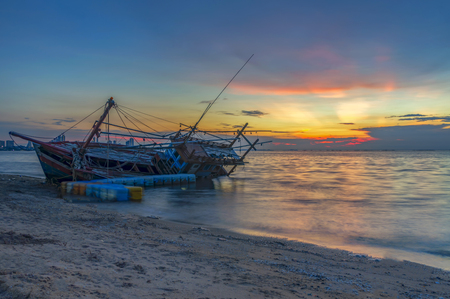 An old shipwreck or abandoned shipwreck. Boat capsized on the sand beach in beautiful colorful twilight sunset background with plastic tank movement, Pattaya of Thailand.
