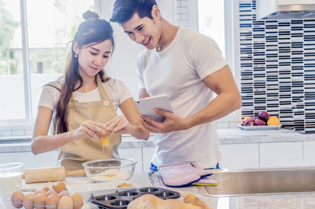 Beautiful asian young couple helping to cooking bekery in the kitchen at home.Man is looking tablet. Stock Photo - 91506419