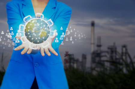 Young businesswoman  holding earth care and love to our planet,Oil refinery industry background.
