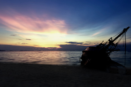 Silhouette of old shipwreck or abandoned shipwreck, Boat capsized on the sand beach in beautiful colorful twilight sunset background with plastic tank movement ,Pattaya of Thailand. Stock Photo