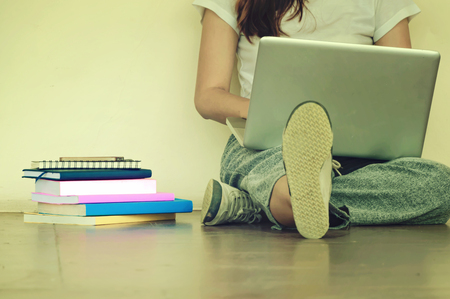 Beautiful woman of a student sitting with laptop and relaxing in the garden. Education concept.Copy space. 스톡 콘텐츠