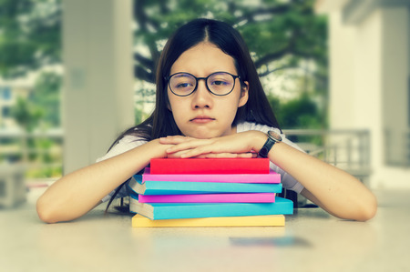 Woman tired student girl with glasses and books on desk, Bored and tired to reading books for exams.University concept. Stock Photo