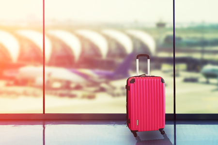 Pink suitcases in airport departure lounge, airplane in background, summer vacation concept, traveler suitcases in airport terminal waiting area. Archivio Fotografico