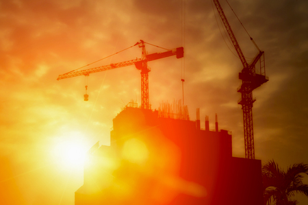 Silhouette of tower cranes and building silhouettes over sun at sunrise. Stock Photo