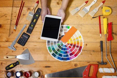 Professional decorator using a digital tablet, work tools, painting rollers and color swatches all around, top view Archivio Fotografico