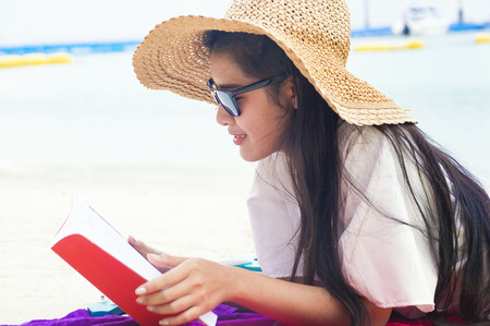 Summer woman relaxing in hipster beach hat and colorful sunglasses. Funky happy girl having fun during travel holidays vacation. Young trendy cool hipster woman reading a book and lying in the sand. Stock Photo