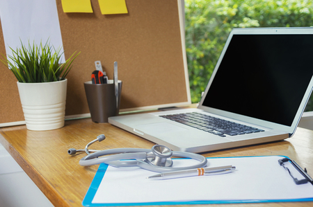 Stethoscope with clipboard and Laptop on desk,Doctor working in hospital writing a prescription, Healthcare and medical concept