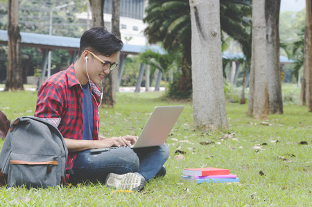Asian attractive male student thinking about coursework strategy sitting in university garden with laptop computer connected to wireless internet,talented editor of online issue creating article