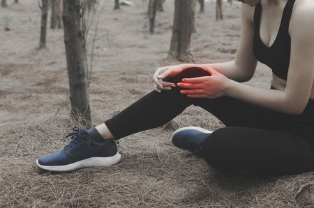 Unhappy young woman sitting in the garden, grabbing an ankle, unable to start running because of sport injury, feeling pain. Beginner doing wrong exercise.