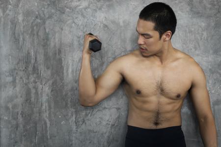 Chico musculoso culturista haciendo ejercicios con pesas en el gimnasio sobre fondo de cemento.
