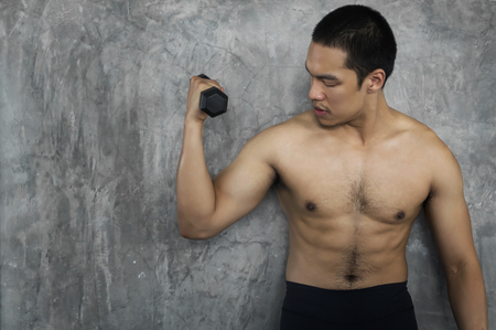 Muscular bodybuilder guy doing exercises with dumbbells in gym on cement background. Stock Photo