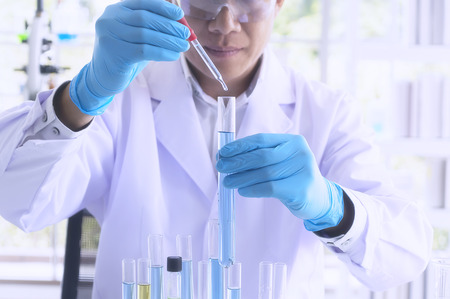 Scientist holding sampling oil or chemical liquid in flask with lab glassware in laboratory background, science or medical research and development concept - Image
