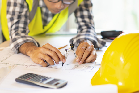 Architect working on blueprint.engineer inspective in workplace - architectural project, blueprints,ruler,calculator,laptop and divider compass. Construction concept. Engineering tools,selective focus