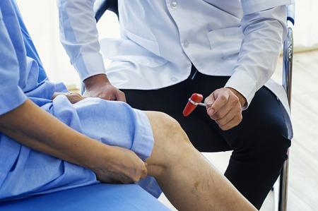 Primo piano del fisioterapista femminile che massaggia la gamba del paziente in una stanza di fisioterapia. Medico dell'uomo che controlla con il martello sensoriale. Archivio Fotografico