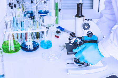 Scientist holding sampling oil or chemical liquid in flask with lab glassware in laboratory background, science or medical research and development concept