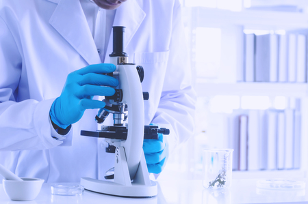 Scientist holding sampling oil or chemical liquid in flask with lab glassware in laboratory background, science or medical research and development concept. Stock Photo