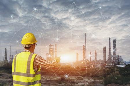Geschäftsmann im Schutzhelm, der den virtuellen Schnittstellenbildschirm als Konzept der Industrie berührt