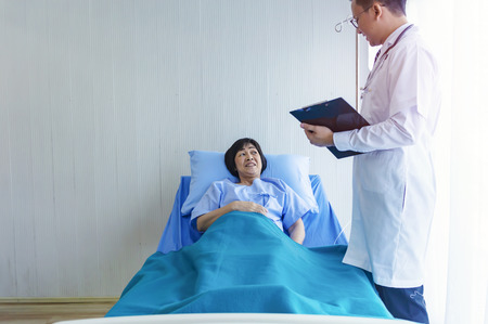 Manndoktor, der den Druck der Patientin überprüft, ältere kranke Patientin lag im Krankenhaus mit intravenöser normaler Kochsalzlösung auf dem Bett. Mediziner, der mit Patienten in der Krankenstation interagiert.