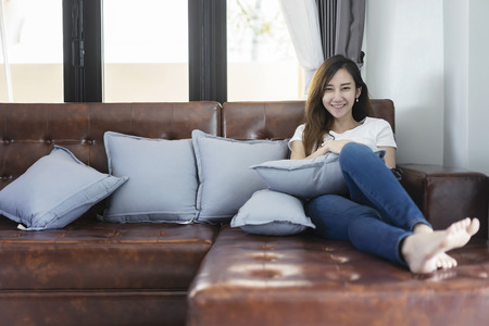 Young smiling woman sitting on sofa. Young woman thinking at home in a leisure time. Happy girl relaxing at home on a bright winter morning.