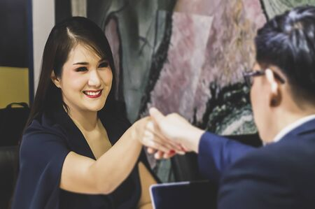 Portrait of smiling female candidate during corporate meeting or job interview with businesswoman holding resume and talking interview - business, career and placement concept