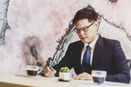 Confident businessman in eyeglasses looking at the paper and working at table with computer monitor in modern office.