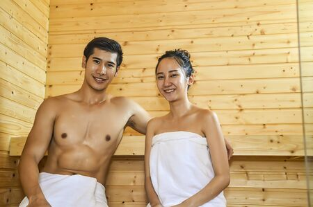 Happy couple relaxing in wooden sauna at home.