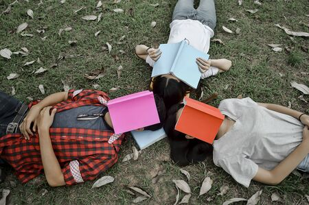 University students are reading a book on the green grass. Stock fotó