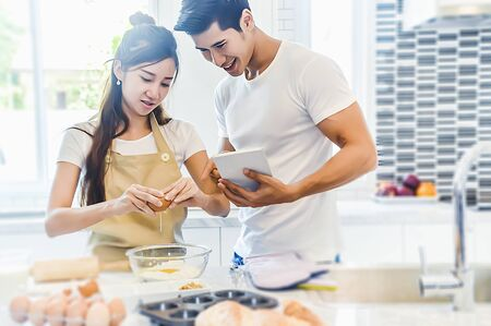 Asian couples cooking and baking cake together in kitchen room. Man and woman looking to each other at home.