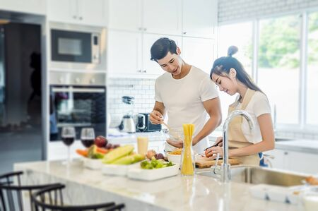 Beautiful asian young couple loving smiling is looking to cooking in kitchen at home,Happy handsome man washing vegetables in the sink and Happy woman feeding food to man.