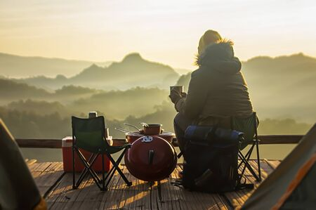 Back view of young tourist woman sitting on blooming valley at tourist tent under beautiful clear blue sky, enjoying foggy mountains view on summer morning. Tourism and traveling concept.