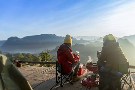 Two women camping in the mountains and drinking coffee. Stock fotó