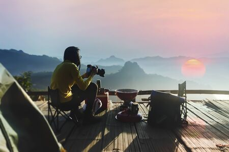 Woman traveler camping take a photo in Mountains with Beautiful summer landscape on background.
