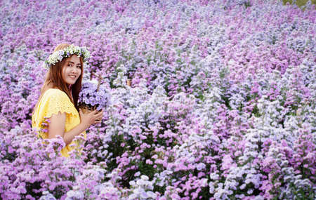 Travel asian adult woman relax in nature sitting in margaret flower field. In yellow shirt style. Trendy famous destination on winter at Chiang mai, Thailand. Joyful woman with bouquet sitting on farm Stock fotó