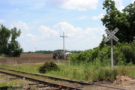 a tractor sitting by railroad tracks and trees photo