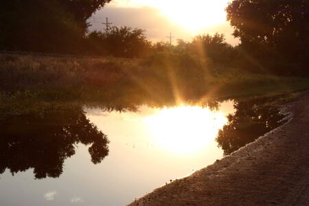 A sunset with two sets of sun rays from the reflection. Stock Photo - 5135474