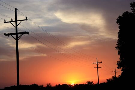 A sun set with telephone poles and wires taken in the country. Stock Photo - 5216050