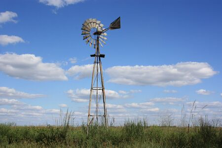 Kansas Windmill in a Pasture with bluesky and white clouds and grass.