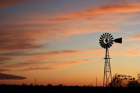 Windmill with clouds,weeds, and sunset.