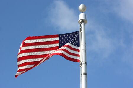 sripes: A US FLAG flying  on a metal flag pole closeup with blue sky. Stock Photo