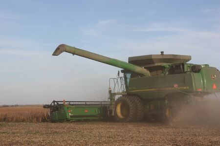 combine: John Deere combine cutting wheat