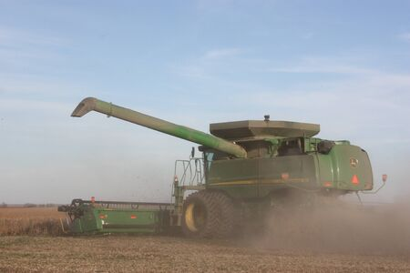 deere: John Deere Combine cutting wheat Editorial