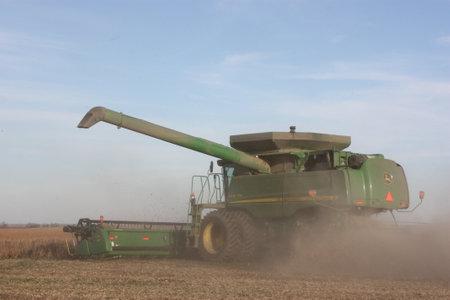 combine: John Deere Combine cutting wheat Editorial