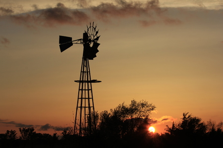 Kansas Sunset with a Windmill Silhouette with trees,and colorful sky. North of Hutchinson Kansas USA out in the Country.