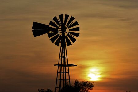 Windmill Silhouette with a Kansas Sunset with clouds. Imagens