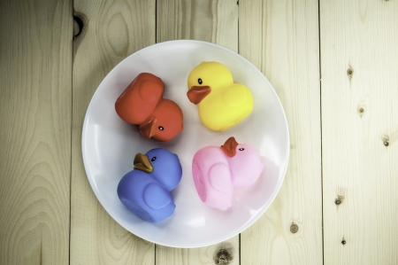 Toy rubber duck on a plate on a wooden floor  photo