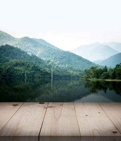 vintage wooden board table in front of dreamy and abstract forest landscape lagoon