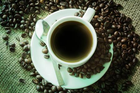 aliments: Caf� noir, mettre sur une plaque � c�t� d'un tas de sacs de grains de caf� en toile de fond.